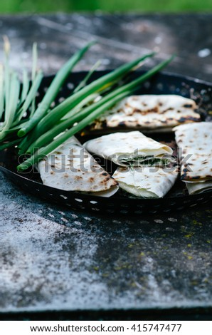 Appetizer of pita with cheese and herbs on the grill - stock photo