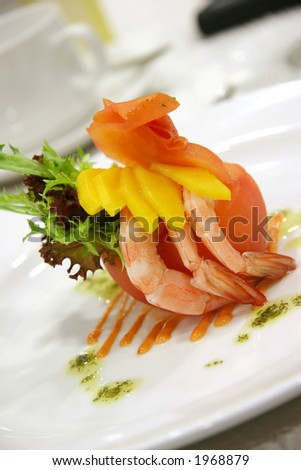 Appetizer of shrimp and mango in a carved out tomato and a dash of different lettuce leaves - stock photo