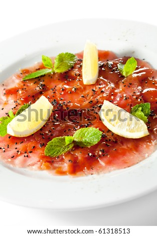 Appetizer - Tuna Carpaccio with Parmesan Cheese, Herbs and Lemon Slice - stock photo