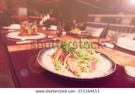 Appetizer with rare fried tuna and salmon on restaurant table, toned image - stock photo