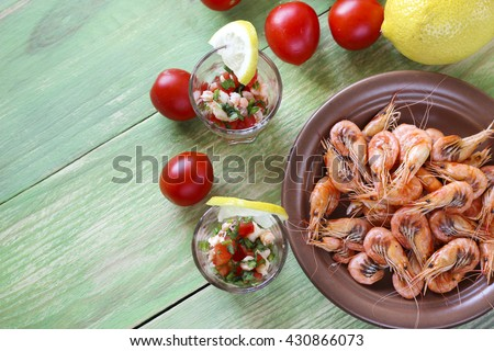 Appetizer with shrimp in small glasses, cherry tomatoes, parsley and lemon, top view - stock photo