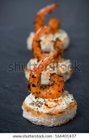 appetizer with spicy shrimps on toast, close-up, vertical - stock photo