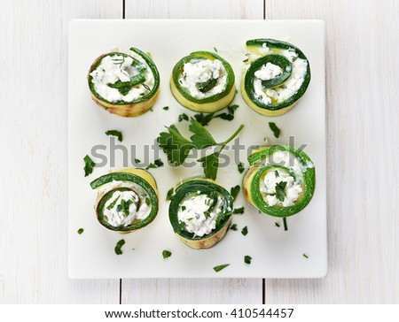 Appetizer zucchini stuffed with curd cheese and green herbs, top view - stock photo