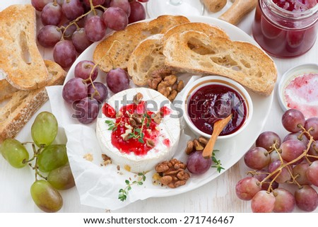 appetizers for wine - camembert with berry jam, toast and fruit on  table, top view, close-up - stock photo