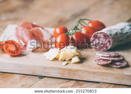 Appetizers - tomato, meat and cheese - on wooden board. Toned image - stock photo