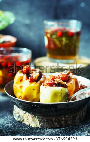 Appetizing baked apples stuffed with raisin and nuts. Baked apples with sweet jam raspberry jam and walnuts on the metal pan. Fresh herbal tea with red berries in glass. Rustic dark style. - stock photo