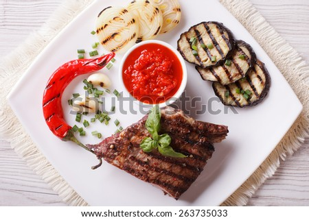 appetizing beef steak, grilled vegetables and sauce on a plate. horizontal view from above  - stock photo