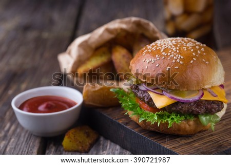 Appetizing homemade burger with beef patty, lettuce, tomato, cheese, pickled cucumbers and red onion served with fried potato and ketchup, on wooden cutting board. Close up view - stock photo