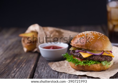 Appetizing homemade burger with beef patty, lettuce, tomato, cheese, pickled cucumbers and red onion served with fried potato and ketchup with glass of cola on background - stock photo