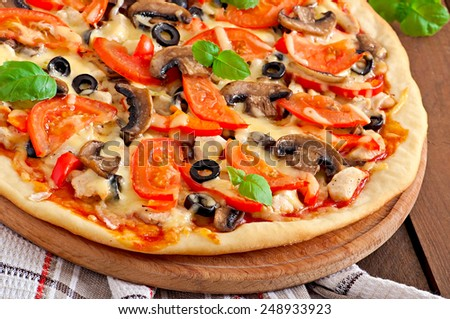 Appetizing pizza with chicken, tomatoes, peppers and mushrooms - stock photo