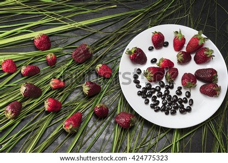 Appetizing strawberry in the grass on a white plate - stock photo