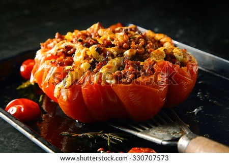 Appetizing stuffed oven roasted ripe tomato with a spicy savory stuffing being displayed on a spatula for healthy starters or accompaniment to dinner - stock photo