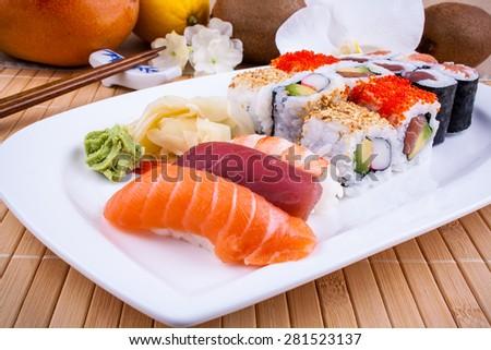 Appetizing sushi with wasabi, fruits and chopsticks closeup - stock photo