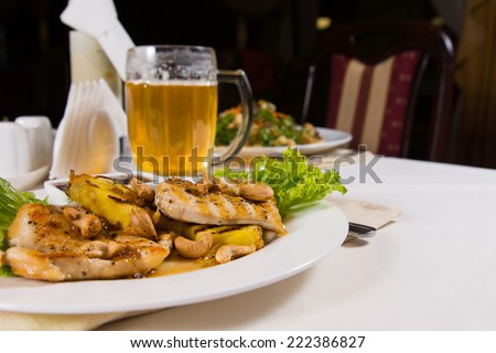 Appetizing Tender Juicy Chicken Meat Main Dish and a Mug of Beer Served on White Table. - stock photo
