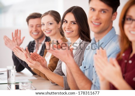 Applauding to you. Group of young people sitting together at the table and applauding to you - stock photo
