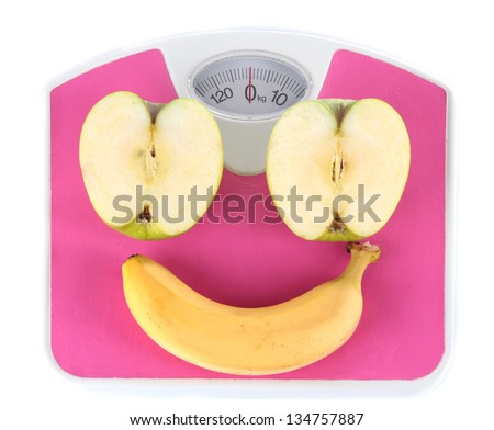 Apple and banana on scales isolated on white - stock photo
