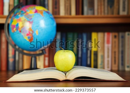 apple and book on background bookcase - stock photo