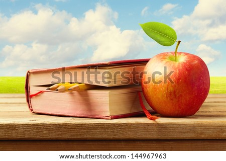 Apple and book with pencils on wooden table over beautiful landscape. Back to school concept - stock photo