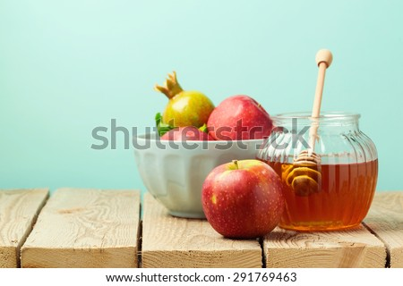 Apple and honey on wooden table over blue background - stock photo