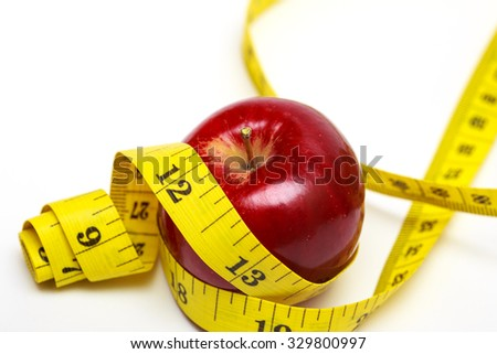 apple and measuring tape on a white background - stock photo