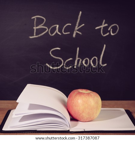 Apple and opened book on the wooden desk with Back To School blackboard background. - stock photo