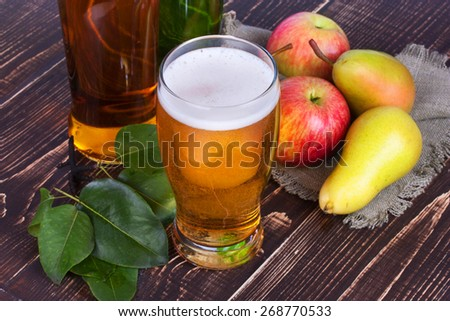Apple and pear cider glass and bottles with fruits - stock photo