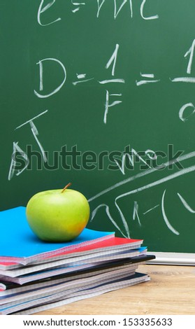 Apple and writing-books against a school board with formulas on the physicist. - stock photo