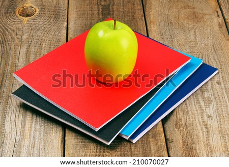 Apple and writing-books on a wooden background. - stock photo