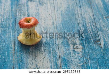 Apple bitten laid out on a wooden floor in blue and white. - stock photo