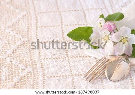 Apple Blossoms with Fork and Spoon on Table with Cream Lace Tablecloth.  Above View horizontal with room or space for text, copy.  Vintage Style - stock photo