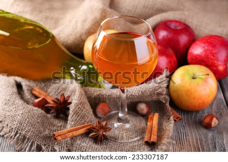 Apple cider in wine glass and bottle, with cinnamon sticks and fresh apples  on table, on dark background - stock photo