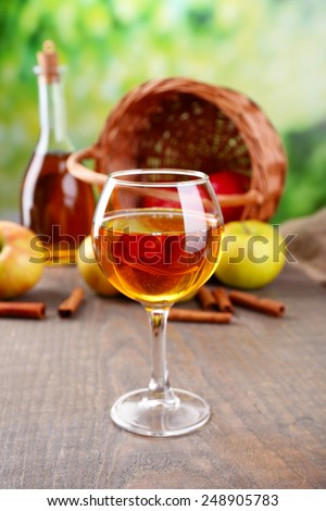 Apple cider in wine glass and bottle, with cinnamon sticks and fresh apples on wooden table, on bright background - stock photo
