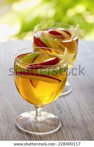 Apple cider sangria with sliced apples in outdoor setting with natural light. - stock photo