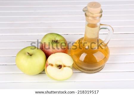 Apple cider vinegar in glass bottle and ripe fresh apples, on wooden table - stock photo