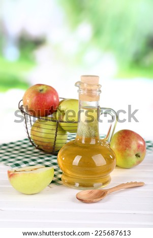 Apple cider vinegar in glass bottle and ripe fresh apples, on wooden table, on nature background - stock photo