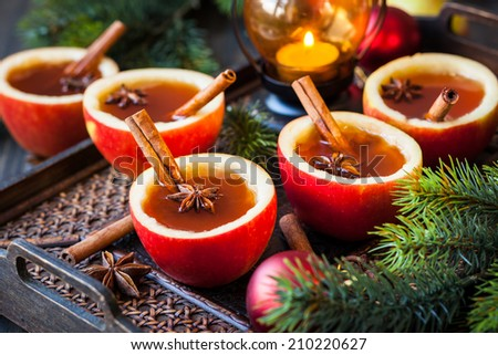 Apple cider with cinnamon sticks and anise star in apple cups - stock photo