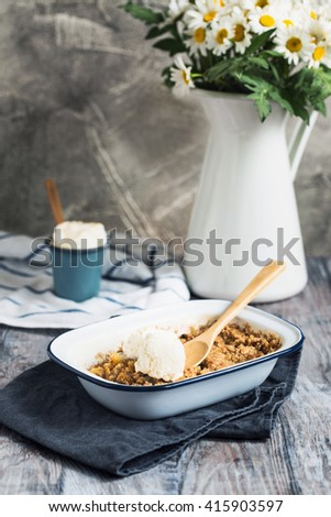 Apple crisp with ice cream in enamel dish with chamomile and rustic background  - stock photo