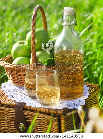 Apple drink and basket with green apples outdoors - stock photo