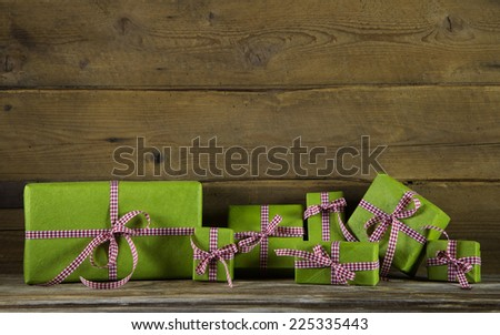 Apple green presents with red and white checked ribbon on wooden background for birthday, christmas or mother's day. - stock photo