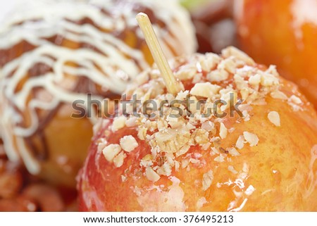 Apple in candy decorated with chocolate and nuts - stock photo