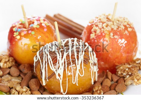 Apple in candy decorated with chocolate, nuts and confectionery sprinkles - stock photo