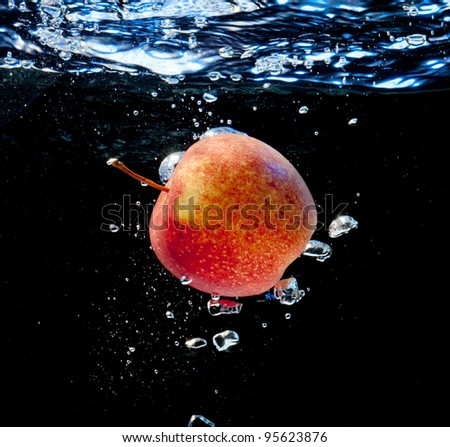 Apple in water with bubbles. on a black background - stock photo