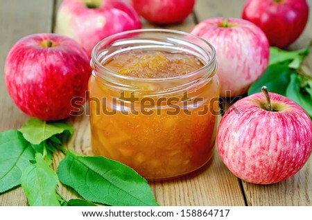 Apple jam in a glass jar, fresh red apples, twigs with leaves on a wooden board - stock photo