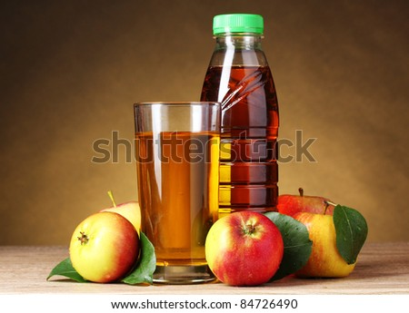 Apple juice and apples on wooden table on brown background - stock photo