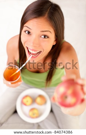 apple juice woman drinking apple juice showing apples. Happy excited and cheerful young female model. - stock photo