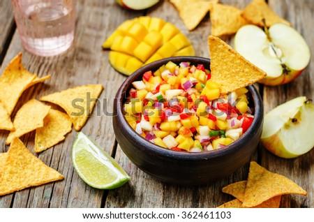 apple mango salsa on a dark wood background. toning. selective Focus - stock photo