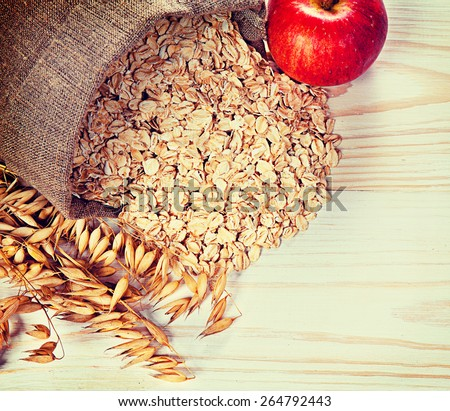 Apple, oats and oat flakes on the table. Vintage retro hipster style version, soft focus - stock photo