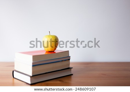 apple on a book pile - stock photo