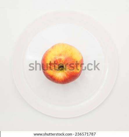 Apple on a white plate with metal cutlers. Fat burning diet illustration - stock photo