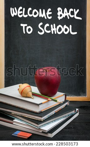 Apple on books and welcome back to school handwritten on the chalkboard in the background - stock photo
